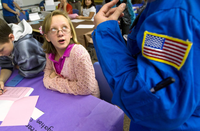 Hillcrest Elementary fifth-grader Sarah VanGrundy speaks to Commander Michelle Wallace of the Challenger Learning Center Monday, Dec. 17, 2012 in Gillette, Wyo., during an exercise in which the fifth-grade class had to solve math and science problems to find a missing satellite.